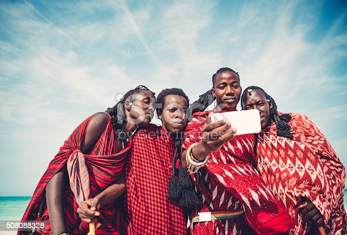 Group of Masai warriors in traditional clothing taking a selfie with smart phone (Zanzibar, Africa).