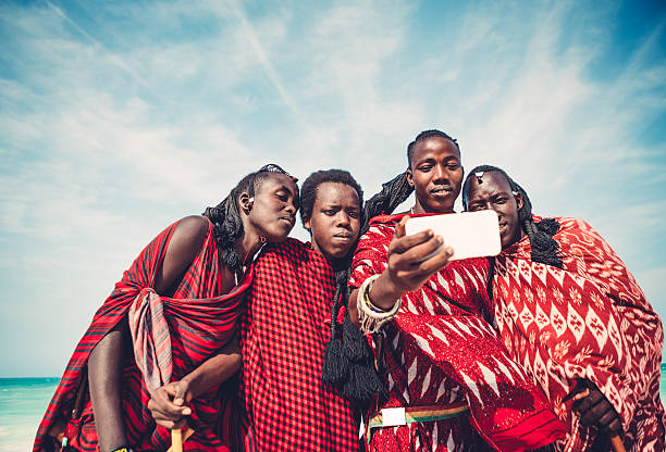 Masai Taking A Selfie Group of Masai warriors in traditional clothing taking a selfie with smart phone (Zanzibar, Africa). developing countries stock pictures, royalty-free photos & images