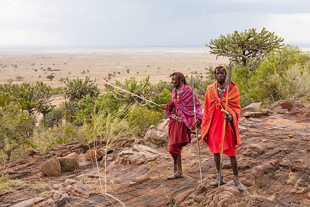 Masai warriors preparing for a hunt Two Masai warriors standing and looking away masai mara national reserve stock pictures, royalty-free photos & images