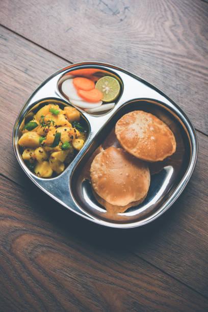 Masala Aloo Sabzi auch bekannt als Bombay Kartoffeln mit gebratenem Puri oder Poori in eine Stahlplatte, selektiven Fokus serviert – Foto