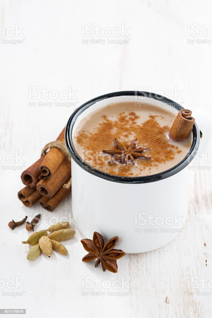 Masala tea in cup and ingredients on white table, vertical stock photo