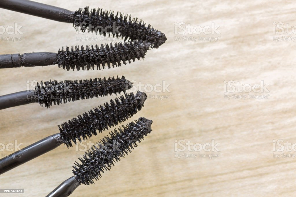 Mascara brushes, cosmetic to enhance eyelashes from different brand on wooden floor with copyspace stock photo