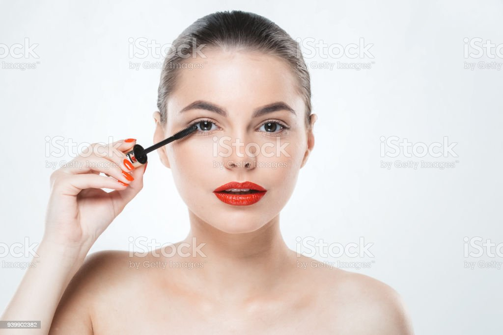 Mascara makeup woman face with red lips and manicure nails isolated on white stock photo