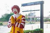 Nakhon Sawan, THAILAND - Mar 01, 2019: Mascot of McDonald's Restaurant, Ronald McDonald standing in front of McDonald's drive thru service sign, McDonald's is an American fast food restaurant chain