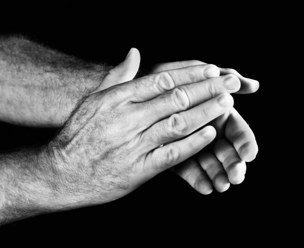 Masculine hands applauding against black background A man's hands applaud against a black background. Black and white image. approbation stock pictures, royalty-free photos & images