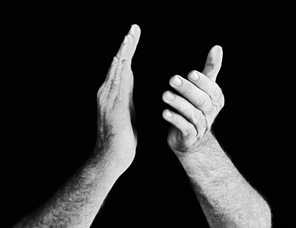 Masculine hands applauding against black A man's hands clap against a black background with copy space. BW. approbation stock pictures, royalty-free photos & images