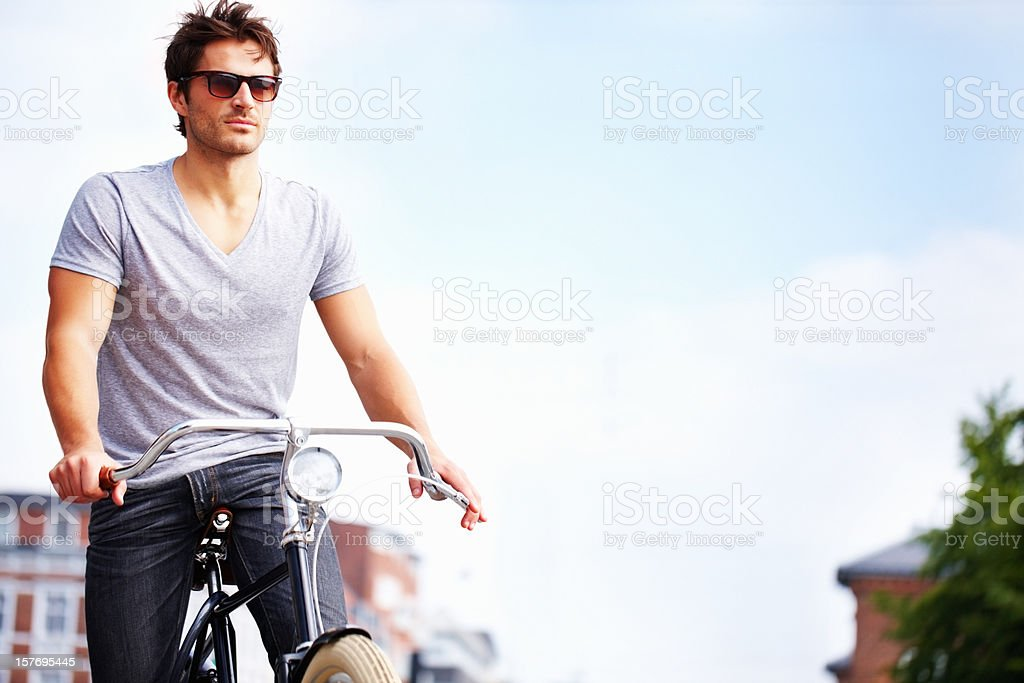 Masculine, young man riding a bicycle - copyspace royalty-free stock photo