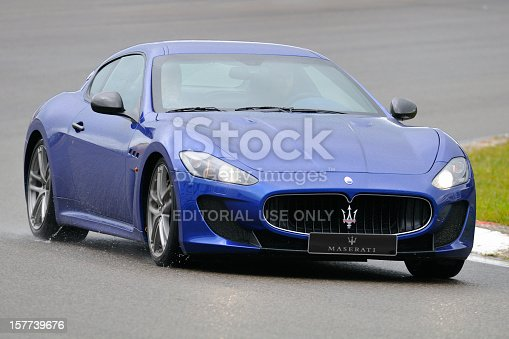Zandvoort, The Netherlands - June 24, 2012: Blue Maserati GranTurismo sports car driving on a wet race track during the 2012 Italia a Zandvoort day. Two persons are sitting inside the car.