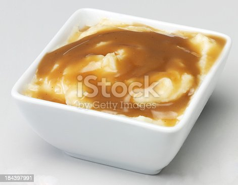 White bowl with creamy mashed potato and savoury brown gravy