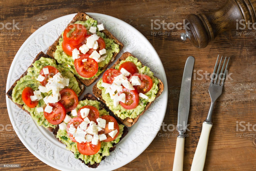 Mashed avocado, tomato and cheese toasts stock photo