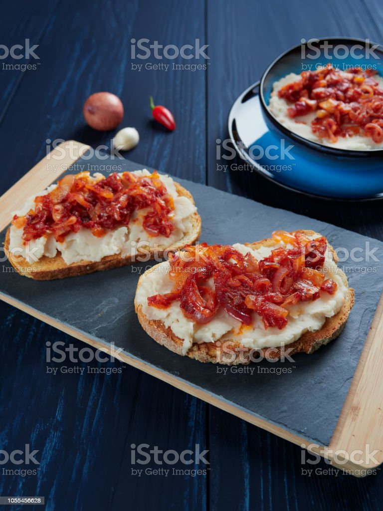 Mashed beans spread with garlic vegetable oil, with a topping of sauteed onions and tomato paste (Romanian: fasole batuta) stock photo