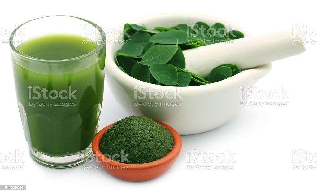 Mashed moringa leaves with extract in a glass stock photo