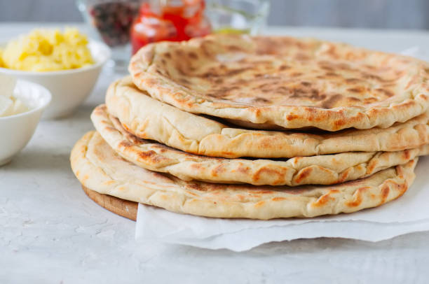 Mashed potato and sheep cheese filling flatbread on a white stone background. Mashed potato and sheep cheese filling flatbread on a white stone background. naan bread stock pictures, royalty-free photos & images