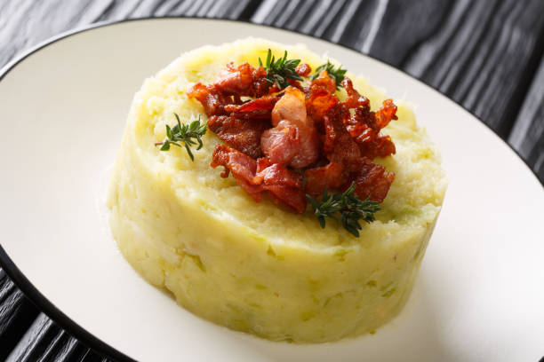 Mashed potatoes and green cabbage topped with fried bacon closeup in a plate. horizontal stock photo