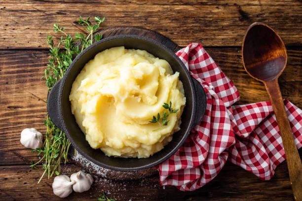 kartoffelpüree, gekochte pürieren in gusseisen topf auf dunklem holz rustikal hintergrund, draufsicht - knoblauchkartoffeln stock-fotos und bilder