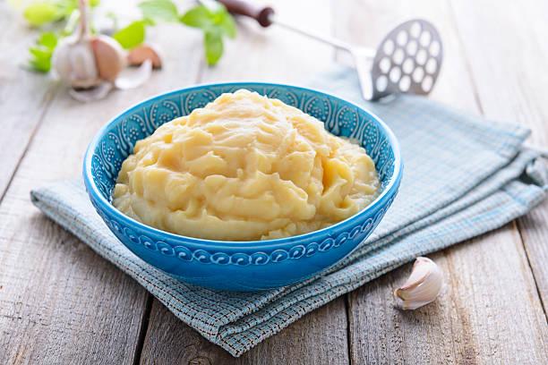 kartoffelpüree in blau schüssel - knoblauchkartoffeln stock-fotos und bilder