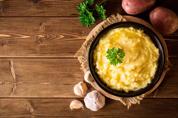 kartoffelbrei mit butter und petersilie in einer schüssel auf rustikalen holztisch - knoblauchkartoffeln stock-fotos und bilder
