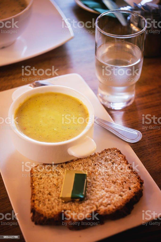 Püresi çorba ve ekmek tereyağı, su üzerinde bir yemek masası ile. - Royalty-free Akşam yemeği Stok görsel