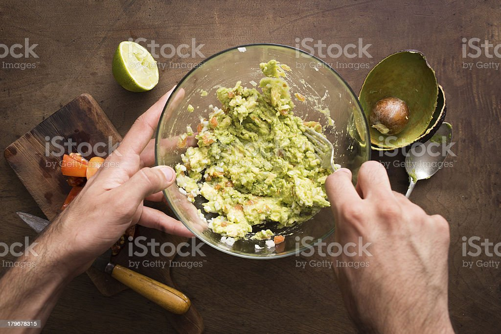 Mashing vegetables to make guacamole stock photo