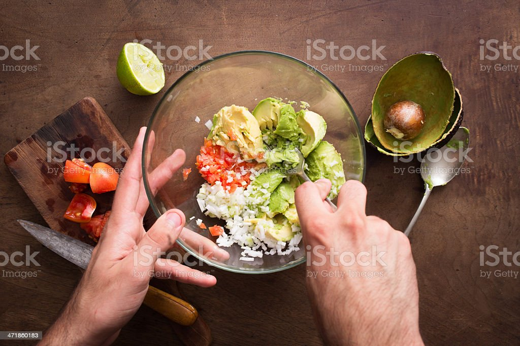 Mashing vegetables to make guacamole royalty-free stock photo