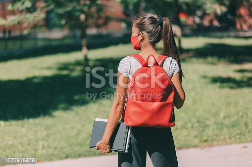 Mask obligatory on campus for back to school university student girl wearing protective face covering walking with books and backpack. College young woman.