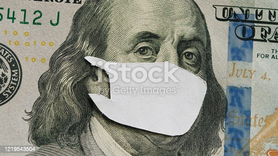 istock mask on dollar bill benjamin franklin - concept of global crisis due to coronovirus infection, pandemic covid-19 1219543504