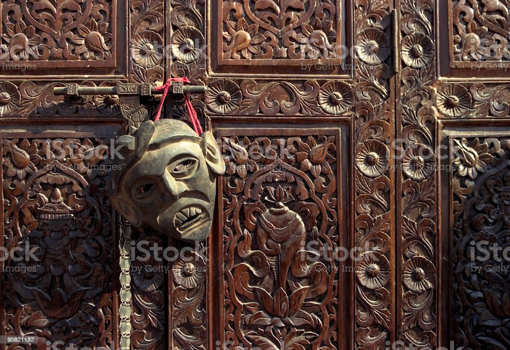 Mask on Wooden Texture of a Door royalty-free stock photo