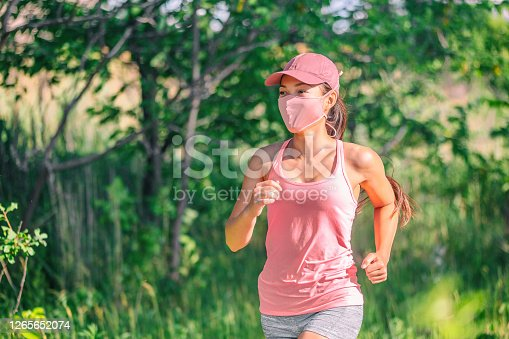 istock Mask wearing during exersice for COVID-19 protection Asian girl running outside with face covering while exercising jogging on run sport workout in summer park nature. Pink mask, cap, tank top 1265652074