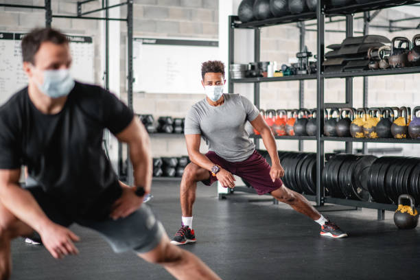 Masked and Distanced Male Athletes Stretching at Gym stock photo