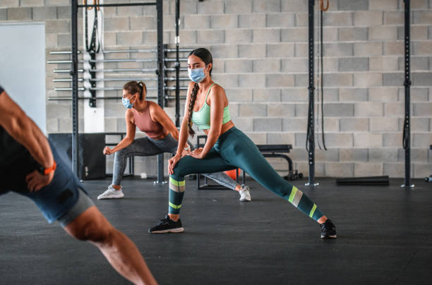Masked and Distanced Mixed Race Athlete Stretching at Gym stock photo