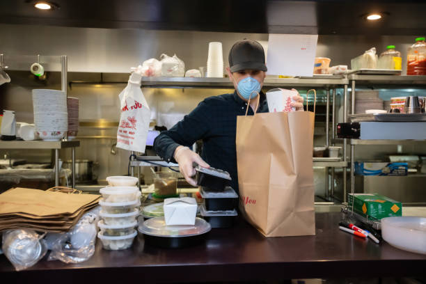 Masked and Gloved Restaurant Worker Packaging Food for Delivery During Covid-19 Outbreak
