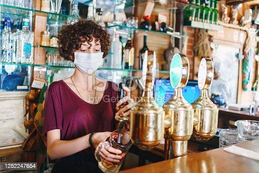 masked bartender filling beer