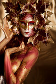 Masked Beauty: close-up portrait of woman with bodypainting wearing a mask on gold background. You might also be interested in these: