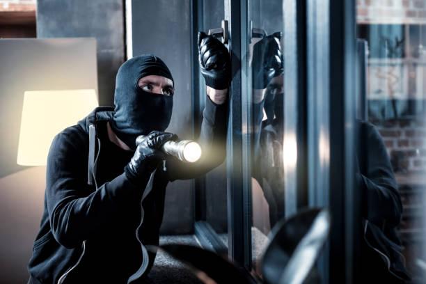 Masked burglar breaking into the house stock photo