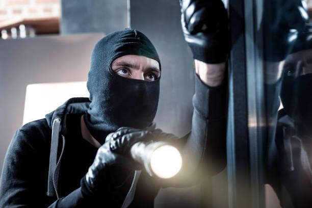 Ladrão mascarado segurando uma tocha - foto de acervo