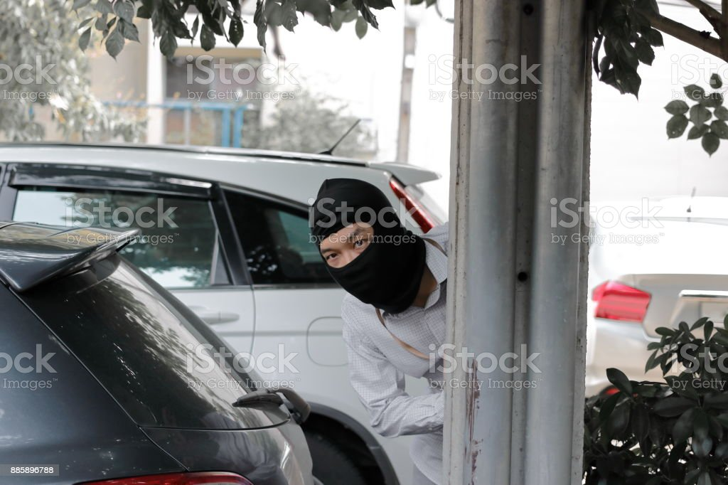 Masked Burglar Wearing A Balaclava And Sneaking Behind Concrete