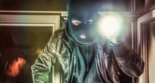 Masked burglar with pistol gun breaking and entering into a victim's home stock photo
