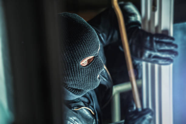 masked burglars breaking and entering into a victim's home stock photo