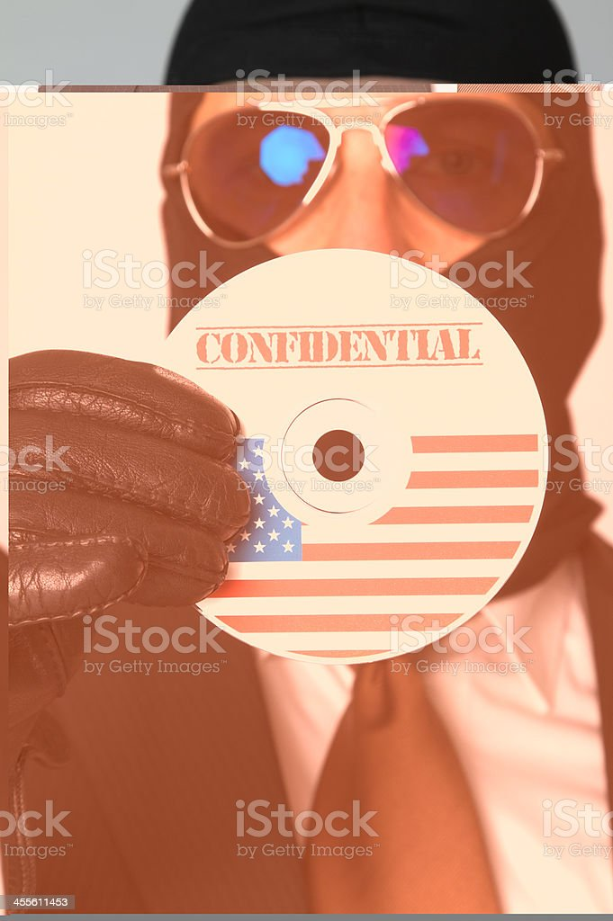 Masked business man stealing confidential data on CD/DVD royalty-free stock photo