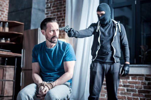 Criminoso mascarado segurando uma pistola à cabeça do homem - foto de acervo