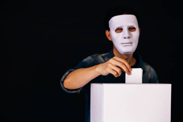 Masked criminal holding ballot paper casting fake vote at a polling station for election vote in black background. Masked criminal holding ballot paper casting fake vote at a polling station for election vote in black background rigging stock pictures, royalty-free photos & images