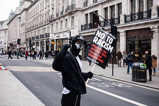 Masked demonstrator poses with anti-racism placard stock photo