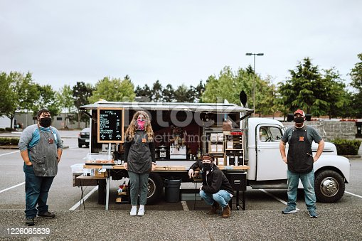 A group of workers wear protective facial masks at their workplace, a coffee food cart in the Seattle, Washington area.  A fun and successful small business.  The outdoor setting is ideal for people to still purchase their coffee and espresso drinks while maintaining social distance during the Coronavirus pandemic. Drew