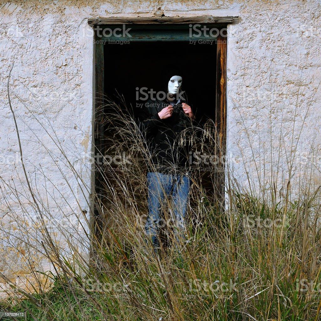 masked figure and broken door stock photo