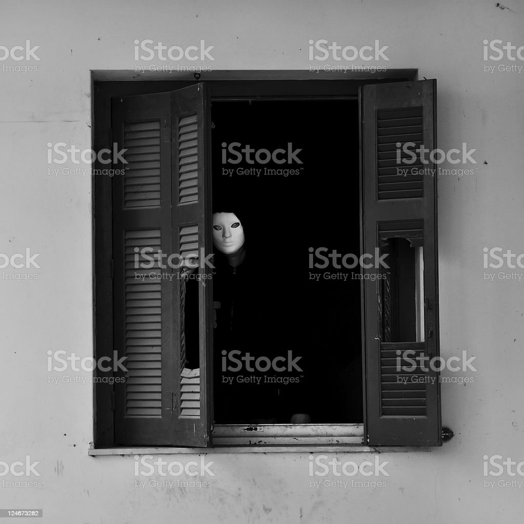 masked figure by broken window stock photo