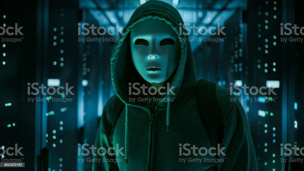 Maskierte Hacker in einem Kapuzenpullover stehen im Corporate Data Center mit Reihen von Rack-Servern arbeiten. – Foto