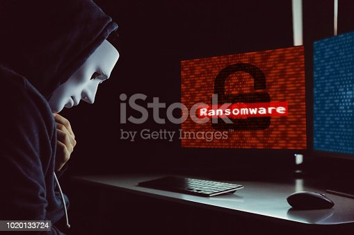 istock Masked hacker under hood using computer to hack into system and employ ransomware - internet computer crime concept. 1020133724