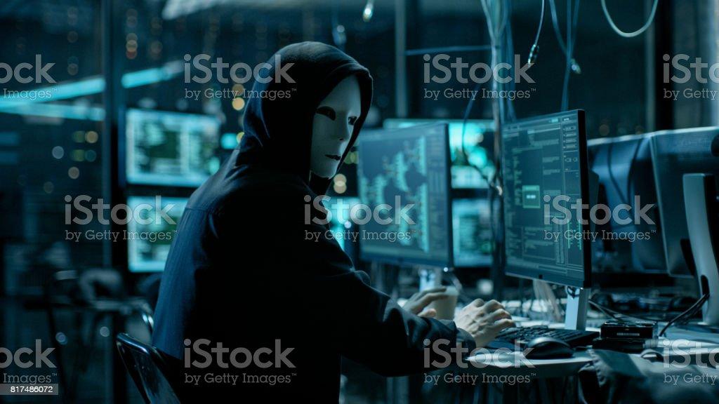 Maskierte Hacktivisten organisiert riesiger Datenmengen Verstoß gegen Angriff auf Unternehmens-Servern. Er ist in unterirdischen Geheimnis Lage umgeben von Displays und Kabel. – Foto