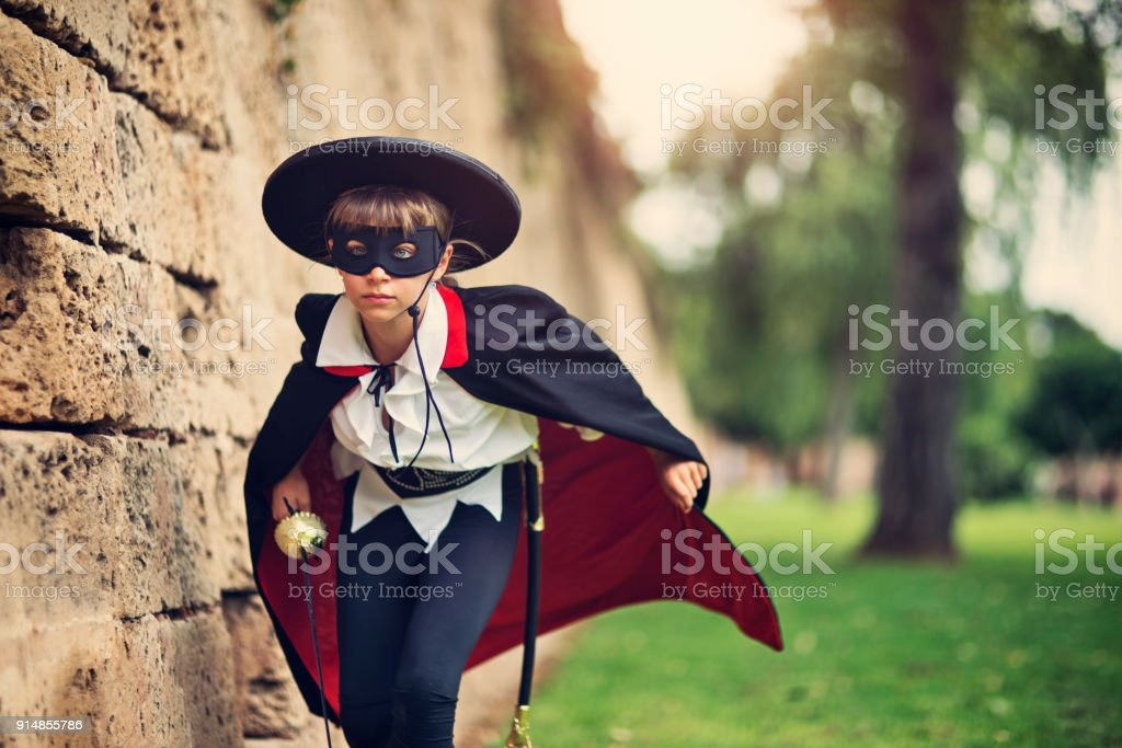 Masked hero girl running to save the day stock photo