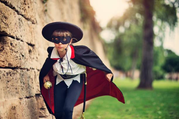 maskierter held mädchen laufen, um den tag zu retten - coole halloween kostüme stock-fotos und bilder